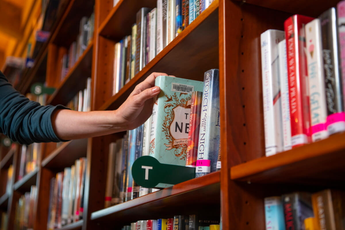 Hand removing book from shelf at Aloha Library