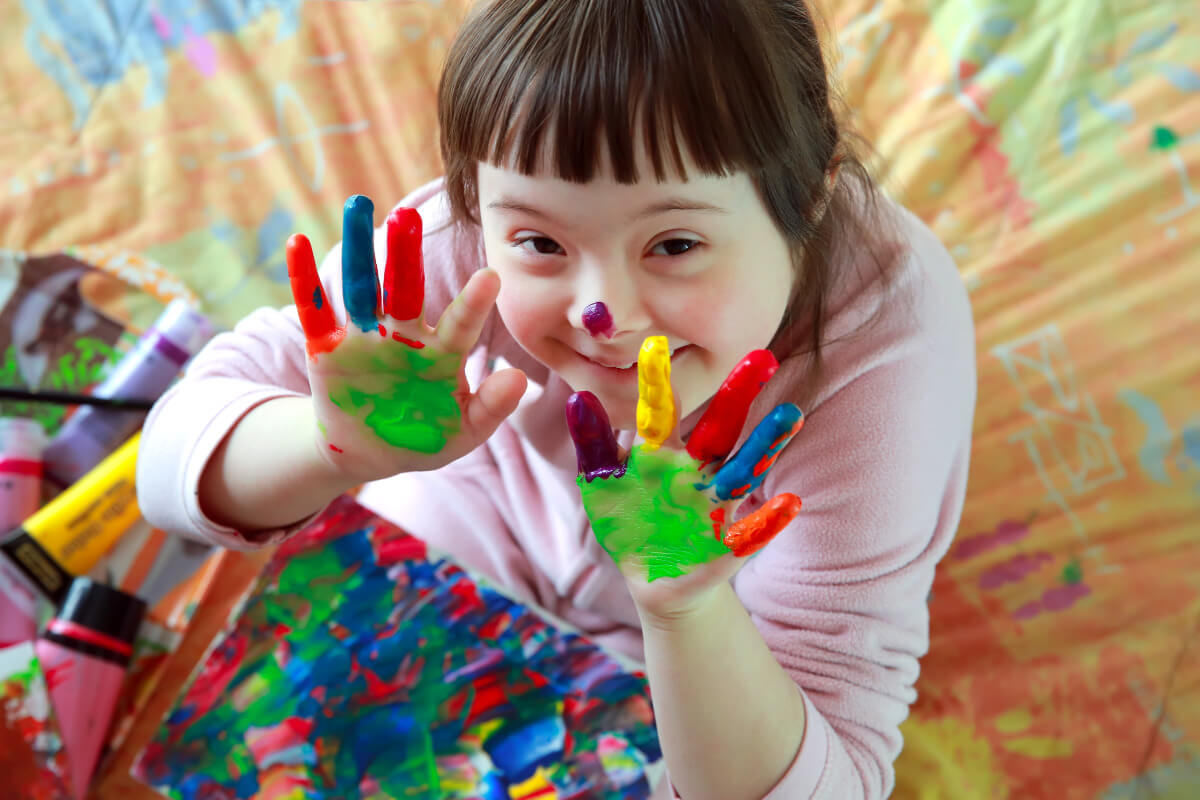Child with fingerpaint on hands, sitting on the floor