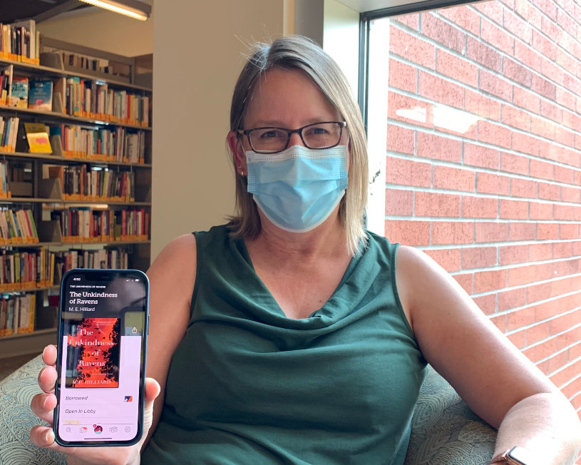Woman wearing a disposable mask and glasses sits by the window in a library reading on her phone.