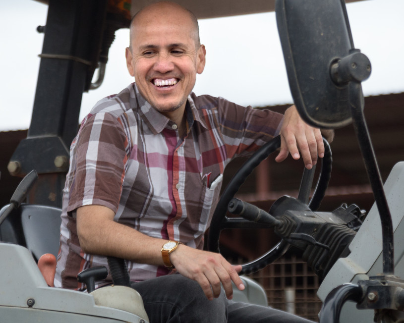 Man wearing a plaid shirt sitting behind the wheel of a tractor
