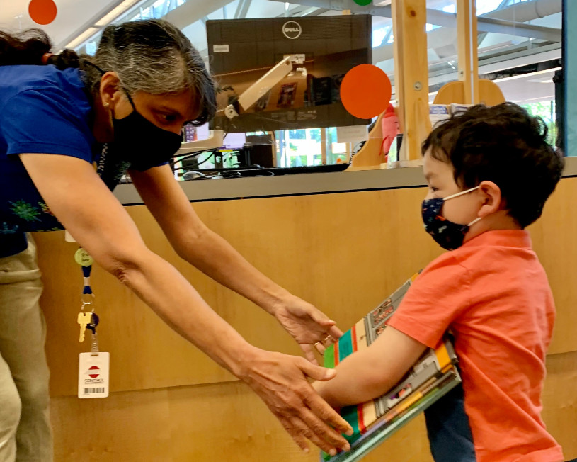 librarian handing books to young boy at service desk