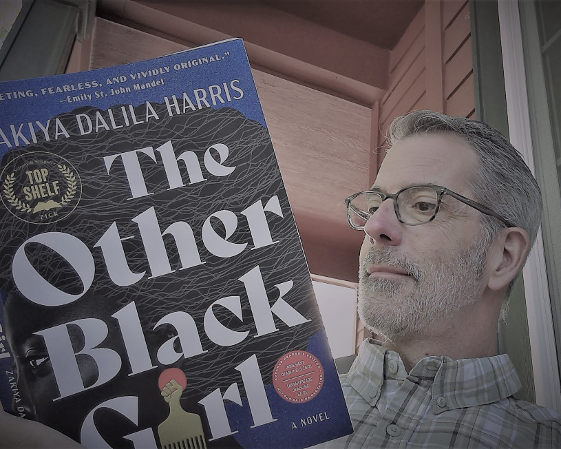 Man with glasses reading The Other Black Girl
