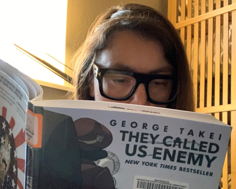 """Woman with glasses reads """"They Called Us Enemy"""" by George Takei."""