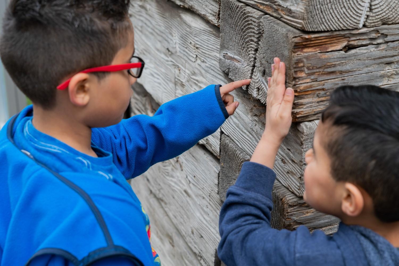 Boys examining old wood wall