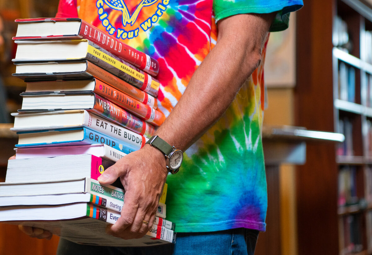 Person in tie-dye shirt holding a stack of books, in the Cedar Mill Library