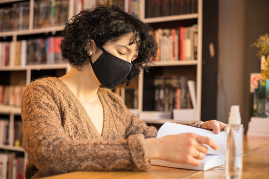 Woman in mask looking at book in library, hand sanitizer on table