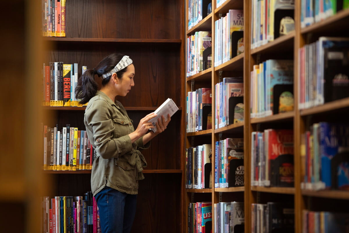 Woman standing in front of shelves at a library, holding a book