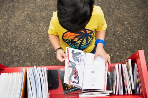Child looking at books on library book cart