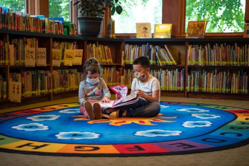 Children looking at books on a round rug in the North Plains Library